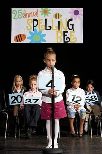 girl-performing-at-spelling-bee-competition-picture-id72822330